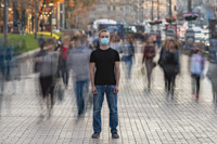 Man with medical face mask stands on the crowded urban street