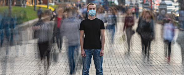 The man with medical face mask stands on the crowded urban street